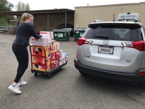 WestSide Baby staff delivering diapers to the car of our provider partner in mask and gloves