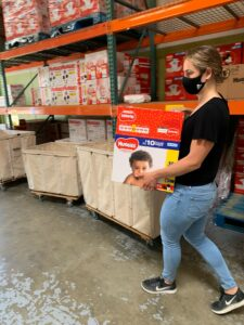 A WestSide Baby staff member carrying a large box of diapers in the warehouse